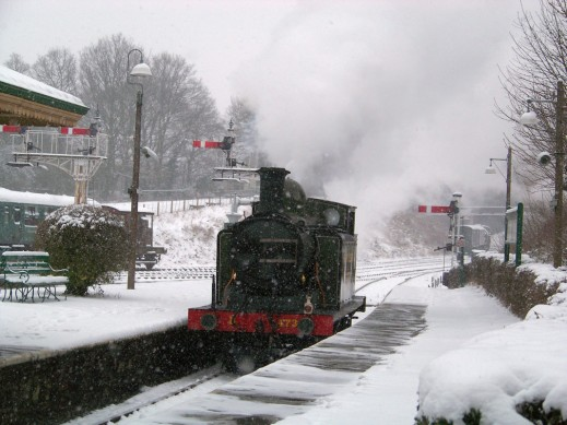 A steam train approaching station in the snow