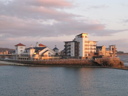 This is the recently regenerated Knightstone Island and Marine Lake. The photo was taken from the roof of the Cove Cafe whilst the sun was setting over Cardiff. Although known as an Island, Knightstone is actually a promontory as it is connected by Knightstone Causeway to the mainland. A pedestrian causeway also extends north-west from the island, this forms the west bank of Marine Lake.